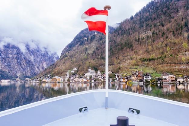 ハルシュタットの風光明媚な写真、夏、オーストリアの黄金の劇的な空の夕日の下でオーストリアアルプスのオーストリアの旗とアプローチフェリーボートからハルシュタット湖で有名な山の村の眺め