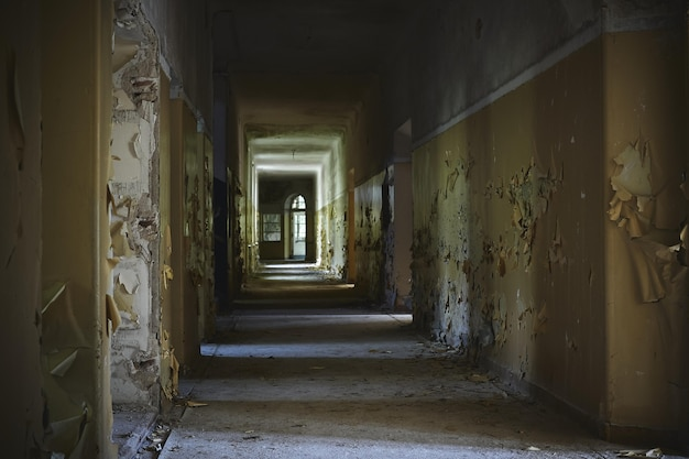 Hallway of an abandoned building with aged walls under the lights
