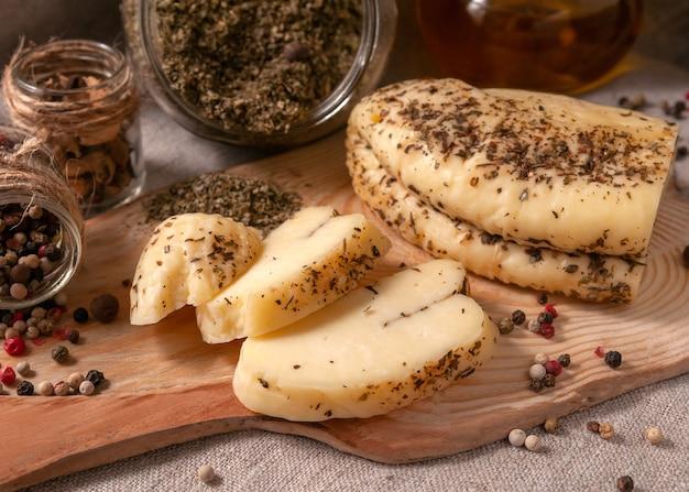 향신료를 곁들인 할루미 치즈는 나무 판자에 얇게 썬다. 향신료로 장식되어 있습니다. 향신료와 올리브 오일이 든 배경 유리 항아리. 확대.