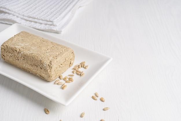 Halva, 또한 halvah, 섬유가있는 흰색 테이블에 접시에 해바라기 씨로 만든 아시아 달콤한 음식