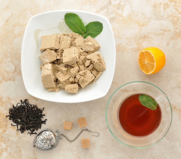 Halva in a plate with mint leaves, black tea in a transparent mug with mint, spoon and sugar cubes on marble surface
