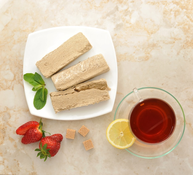 Halva on a white plate with lemon tea and strawberries