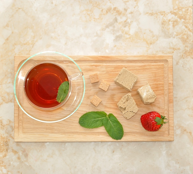 Halva on a white plate with tea and strawberry