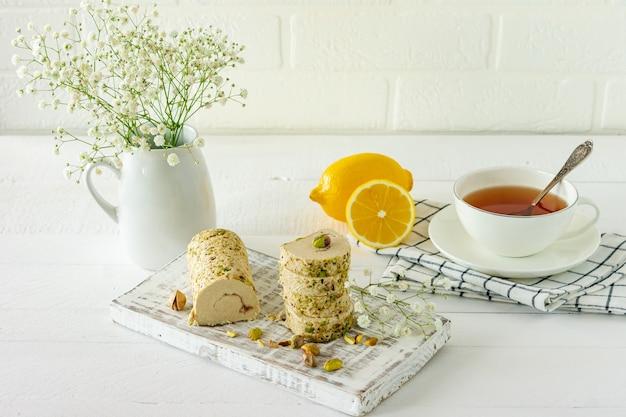 흰색 나무 책상에 꽃과 차를 곁들인 피스타치오를 곁들인 할바.