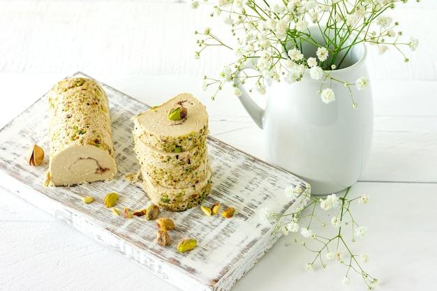 흰색 나무 책상에 꽃과 피스타치오를 곁들인 할바.