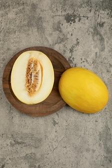 Нарезанные пополам и целые вкусные желтые дыни на деревянной тарелке.