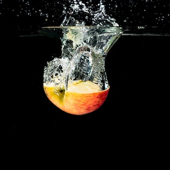 Halved apple with water splash on black background