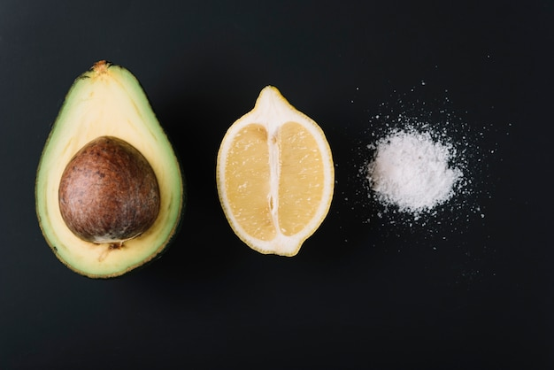 Наполовину авокадо и лимон около соли на черной поверхности