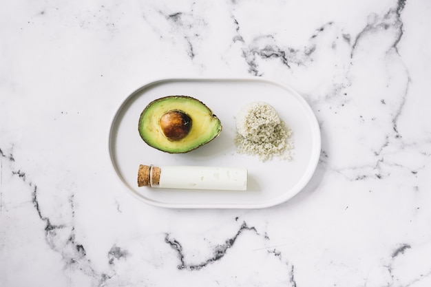 Halved avocado; grated body scrub and test tube on white tray against marble textured background