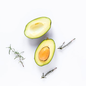Halved avocado and herbs against white background