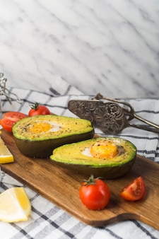 Halved avocado with egg york; tomatoes and lemon slice on chopping board over the napkin with antique tong