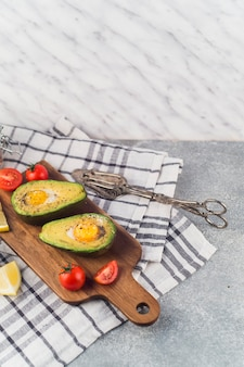 Halved avocado with egg york; tomatoes and lemon slice on chopping board over the napkin with tong