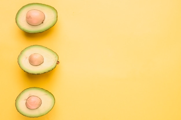 Halved avocado on yellow backdrop