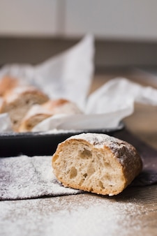 Halved baked bread with flour on wooden table