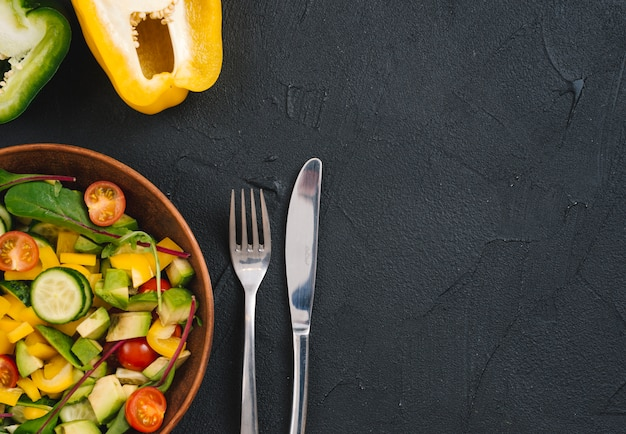 Halved bell pepper and mixed vegetable salad with cutlery on black concrete backdrop