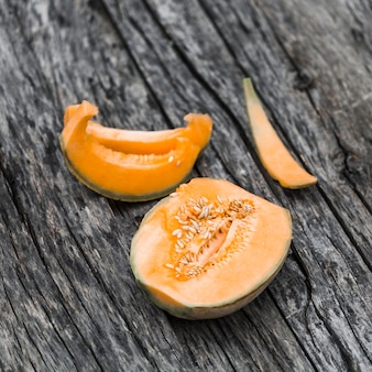 Halved cantaloupe on an old wooden table