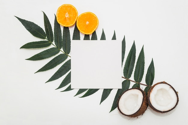 Halved coconut; juicy oranges and blank paper on green leaf against white backdrop