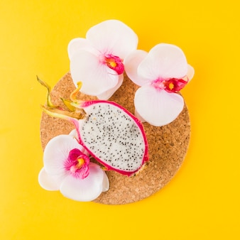 Halved dragon fruit an orchid flowers on cork coaster against yellow backdrop