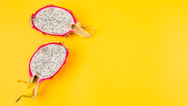 Halved dragon fruit on yellow background