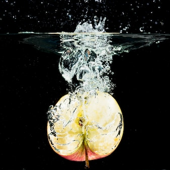 Halved fresh apple falling into clean water against black background