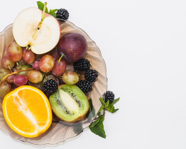 Halved fruits; blackberries and grapes in the bowl on white background
