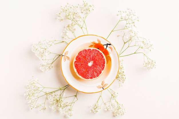 Halved grapefruit on ceramic plate decorated with baby's-breath flowers on white background
