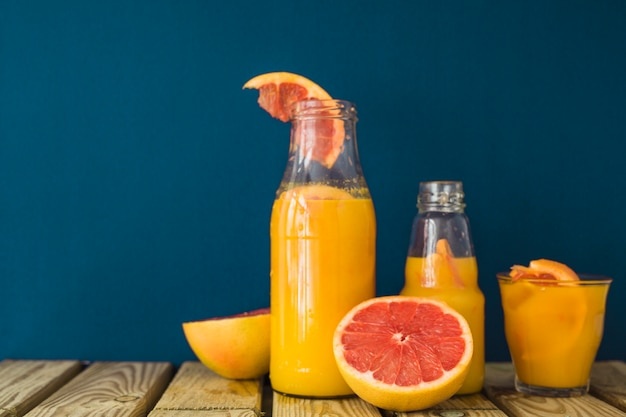 Halved grapefruit and juice in the bottles and glass on table against blue background