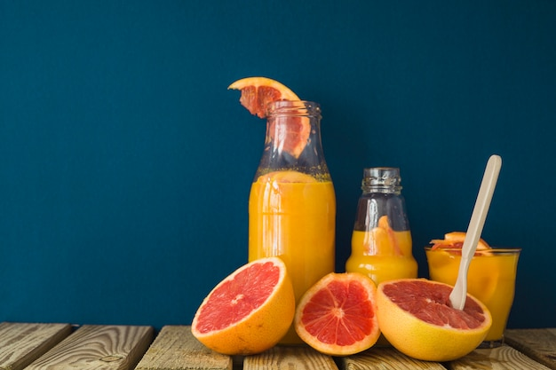 Halved grapefruit with juice on table against blue background