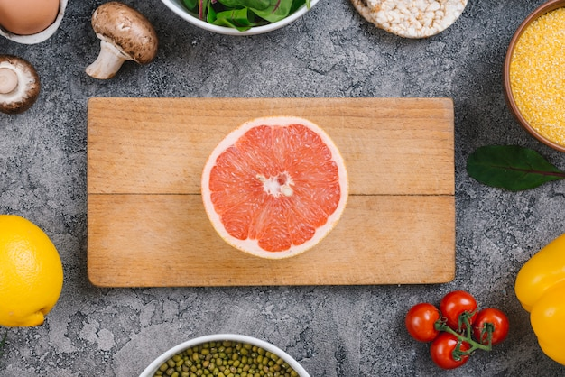 Halved grapefruit on wooden chopping board surrounded with vegetables on gray concrete backdrop