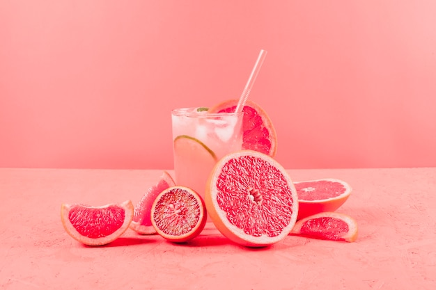 Halved grapefruits and glass of juice on coral background