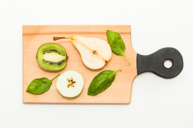 Halved kiwi; pears; apple and basil on chopping board against white background
