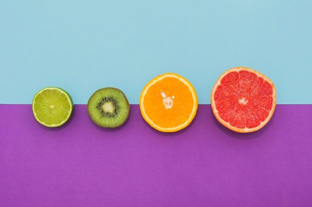 Половинки лимона; киви; оранжевые и виноградные фрукты на двойном фоне