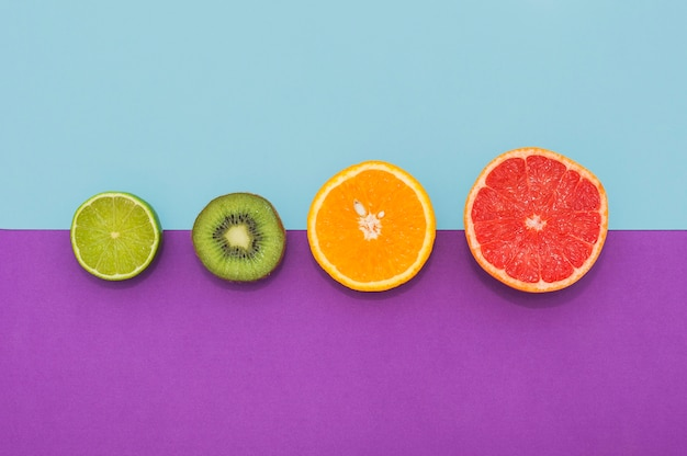 Halved lemon; kiwi; orange and grape fruits on dual background