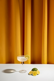 Halved lemon slices near the cocktail on table against curtain
