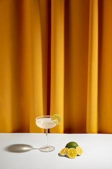 Половинки ломтиков лимона возле коктейля на столе против занавеса