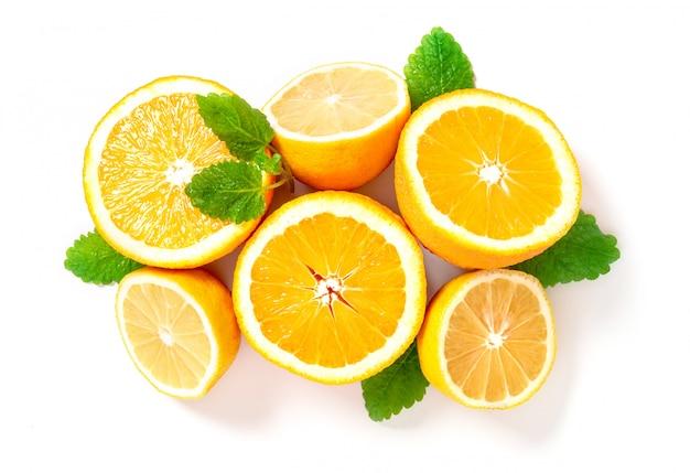 Половинки лимонов и апельсинов лежат в ряд, вид сверху. цитрусы и листья мяты для приготовления лимонада, копией пространства.