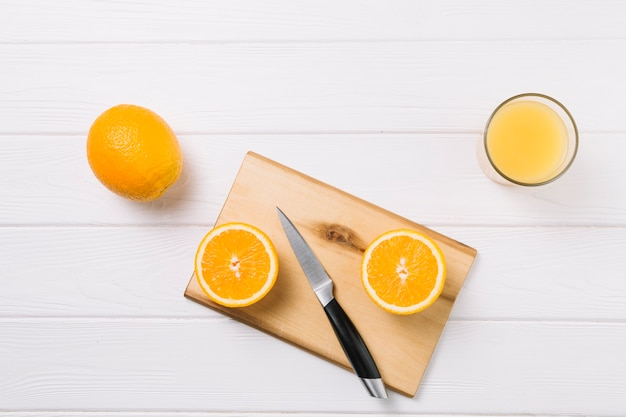Halved orange on chopping board with glass of juice on white table