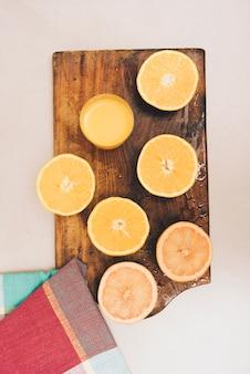 Frutta arancione divisa in due sul tagliere e sul tovagliolo sul contesto bianco