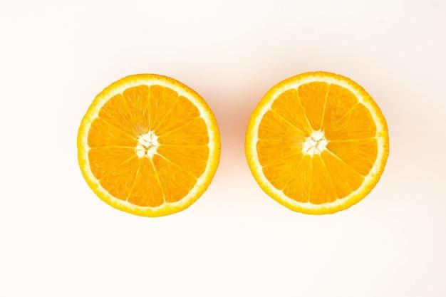 Разрезанный вдвое апельсин на белом фоне, вид сверху