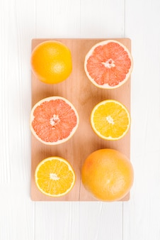 An halved oranges and grapefruits on chopping board over white table