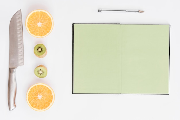 Halved oranges; kiwi; knife; pen and blank page notebook on white background