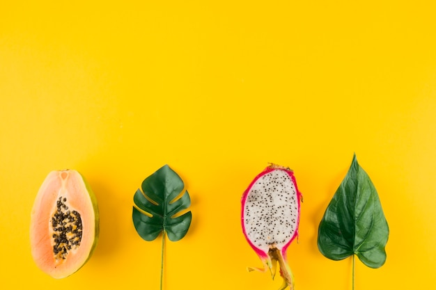 Halved papaya and dragon fruit with artificial leaves on yellow backdrop