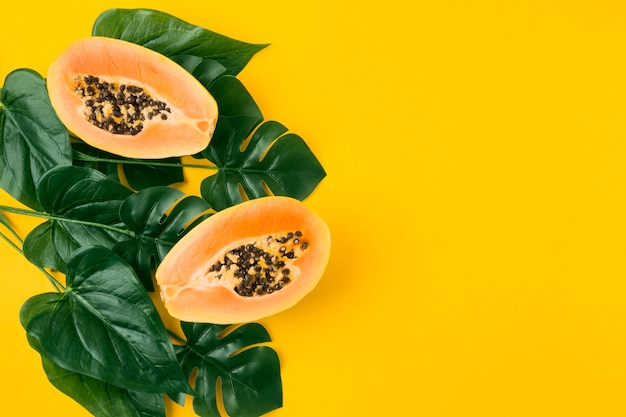 Halved papaya fruit with green artificial leaves on yellow background