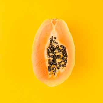 Halved papaya fruit on yellow background