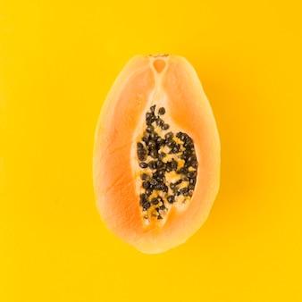 Halved papaya fruit on yellow background