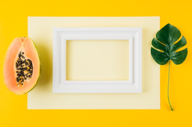 Halved papaya; monstera leaf and white wooden frame on paper against yellow background