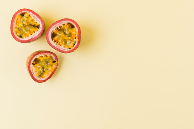 Halved passion fruits on beige background