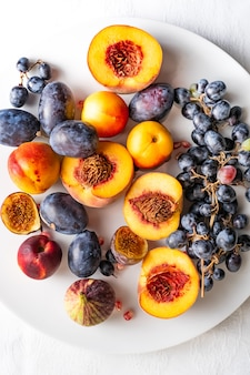 Halved peaches with nectarines and grapes on white plate