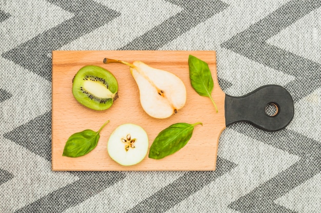 Halved pear; apple slice and basil leaves on wooden chopping board