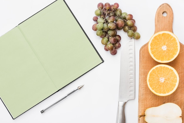 Halved pear; orange fruits on chopping board with bunch of grapes; knife; pen and notebook on white background